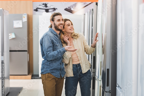 smiling boyfriend pointing with hand and girlfriend touching fridge in home appl Wallpaper Mural