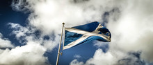 Low Angle View Of Scottish Flag Waving Against Cloudy Sky