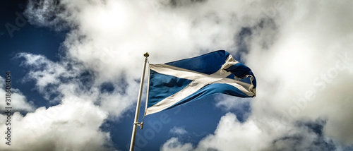 Fotografia Low Angle View Of Scottish Flag Waving Against Cloudy Sky