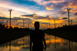 Silhouette Man Standing By River Against Sky During Sunset