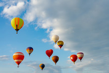 Colorful Hot Air Balloons Flying In Blue Sky. Few Colorful, Hot Air Balloons Descending At The Balloon Festival.
