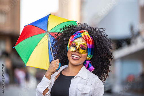 Obraz Young curly hair woman celebrating the Brazilian carnival party with Frevo umbrella on street. - fototapety do salonu