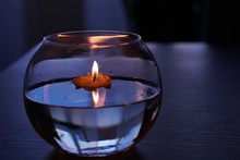 Close-Up Of Lit Candle On Water In Bowl