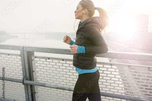 Leinwand Poster Blond hair female jogging outdoors on cold winter day.