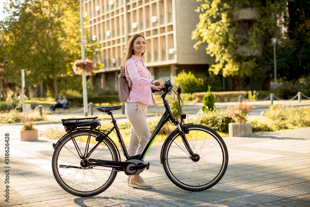 Fototapeta Young woman with modern city electric e-bike clean sustainable urban transportation
