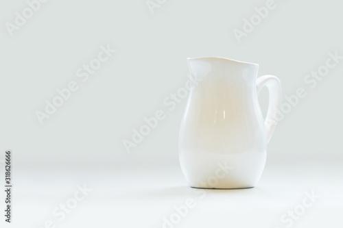 Fototapeta White porcelain milk jug on white background. Pitcher obraz