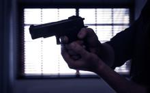 Man Holding Gun Near Window In...