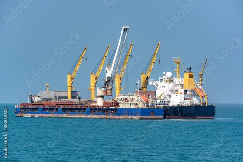 Fotografering Loading ocean-going bulk carrier ship with Bauxite aluminum ore from the mini bulk carrier (feeder) vessel at offshore Kamsar port, Guinea, West Africa