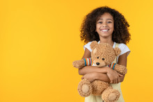 Portrait Of Smiling African Girl Hugging Teddy Bear Toy Isolated On Yellow Background
