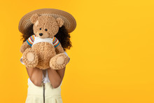 Cute Kid Girl Hiding Over Teddy Bear Toy Isolated On Yellow Background