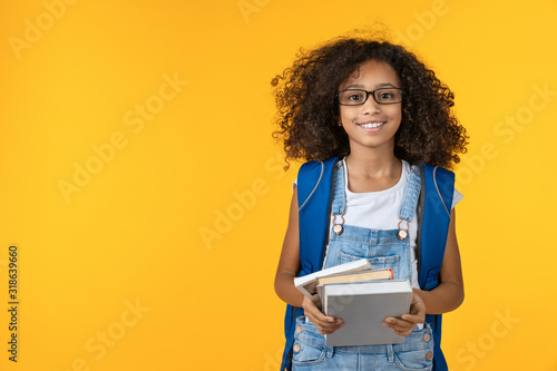 Fotografija Cheerful young african girl kid in eyeglasses holding notebook and books for stu