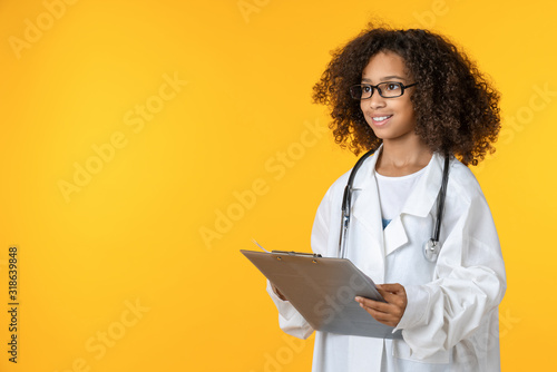 Fotografía Cute little girl dressed like doctor with notepad isolated on yellow background