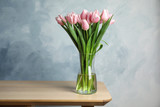 Fototapeta Tulipany - Beautiful pink spring tulips in vase on wooden table