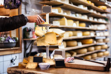 Woman Tasting And Choosing Organic Dutch Cheese On The Shop