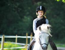 Portrait Of Girl Horseback Riding On Field