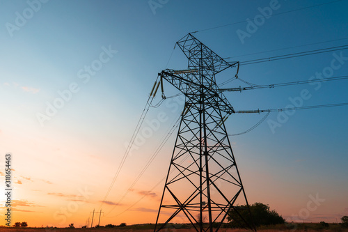Fotografija The silhouette of the evening electricity transmission pylon