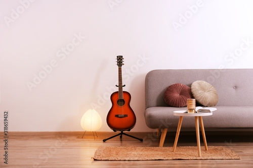Obraz Minimalistic interior design concept. Acoustic guitar on grey textile sofa in spacious room of loft style apartment with wood textured laminated flooring. Background, copy space, close up. - fototapety do salonu