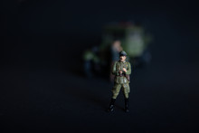 A Figure Of A Man In A Military German Uniform. In The Background Of A Vague Truck