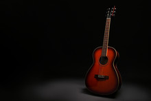 Folk Style Parlor Acoustic Guitar In Darkness On Black Background With A Lot Of Copy Space For Text. Studio Shot Of Travel Size Musical Instrument. Close Up.