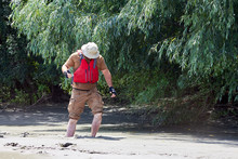 Man Standing In Natural Quicksand River, Clay Sediments, Sinking, Drowning Quick Sand, Stuck In The Soil