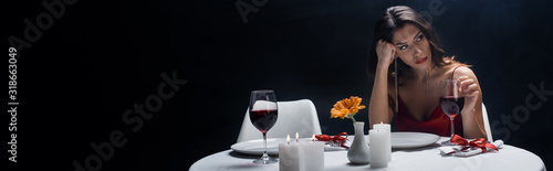 Photo Panoramic shot of boring woman looking away at served table isolated on black