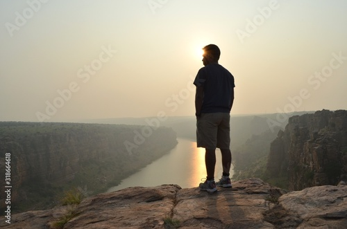Fotomural Rear View Of Man Standing On Cliff Above River At Sunset