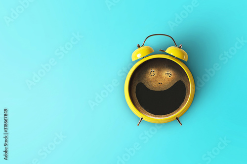 Photo Creative coffee with a smile and a yellow alarm clock on a blue background