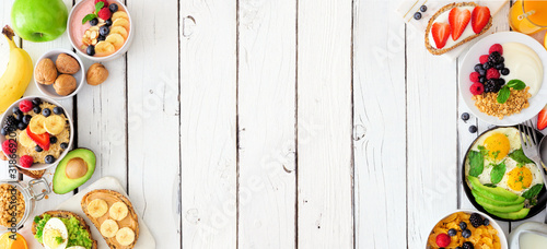 Fototapeta Healthy breakfast food banner with double border. Table scene with fruits, yogurt, smoothie bowl, nutritious toast, oatmeal, cereal and eggs. Top view over a white wood background. Copy space. obraz
