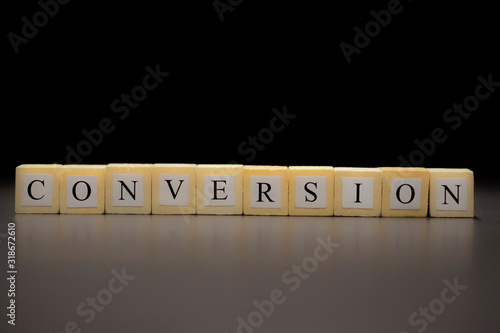 The word CONVERSION written on wooden cubes isolated on a black background Wallpaper Mural