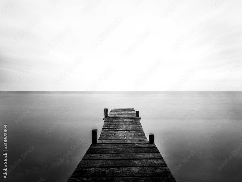 Greyscale of a wooden bridge on the sea under the sunlight and a cloudy sky