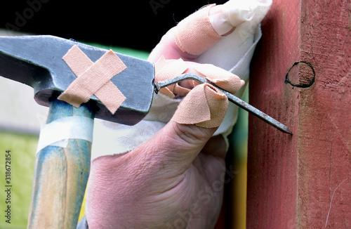 Obraz na plátne Close-Up Of Injured Hand Hammering Nail On Wood