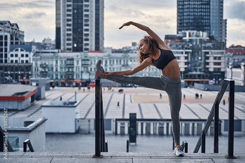 Young athletic woman stretching on the city background , lifestyle training