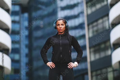 fototapeta na szkło Young woman in black sportswear ready for jogging in the city