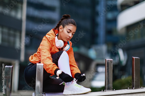 Foto Young woman in an orange hoodie ready for jogging in the city