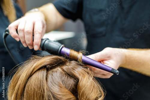 Professional hairdresser twisting the hair with a curling iron in beauty salon, close up.