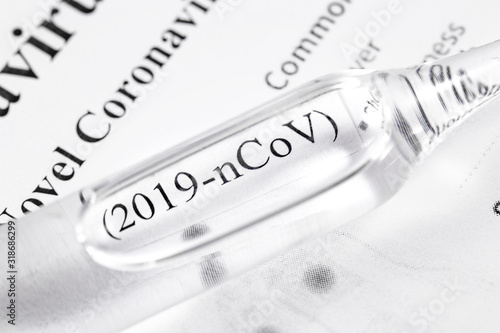 Fototapeta Novel coronavirus (2019-nCoV). Flask with text (2019-nCoV) on paper background closeup, macro obraz