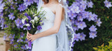 Wedding bouquet of purple and white eustomas close-up in the hands of the bride in a white dress with a veil. Flower portrait in nature. Photography, concept.