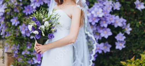 Fotografía Wedding bouquet of purple and white eustomas close-up in the hands of the bride in a white dress with a veil