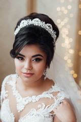 Kind of bride girl in veil and jewelry at home, romantic atmosphere of the bride's morning. Wedding makeup and hairstyle. Glamorous face. Morning of beautiful bride. Wedding day