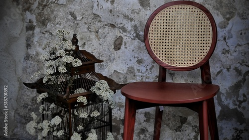 Photo Empty Chair By Flower Buds In Birdhouse Against Old Wall