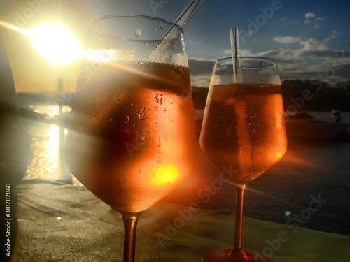 Fotografering Close-Up Of Alcoholic Drinks Against Sky During Sunset
