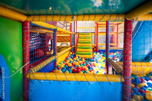 Nowoczesny plac zabaw dla dzieci na świeżym powietrzu do aktywnych gier i rozwoju umiejętności motorycznych. Suchy basen z kolorowymi kulkami. Plac zabaw dla dzieci z kolorowymi matami, sieciami i drutami.
