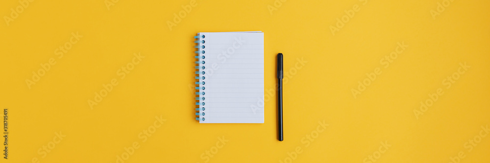Fototapeta Wide view image of blank spiral note pad and black marker