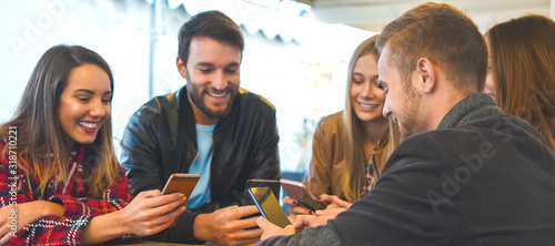 Obraz A group of people standing with their smartphones in hand and enjoying online stuff- Friends using celphones and shareing moments- Technology concept - fototapety do salonu