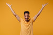 Smiling young african american guy in casual t-shirt posing isolated on yellow orange wall background, studio portrait. People emotions lifestyle concept. Mock up copy space. Rising spreading hands.