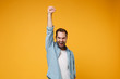 Joyful young bearded man in casual blue shirt posing isolated on yellow orange wall background, studio portrait. People lifestyle concept. Mock up copy space. Clenching fist like winner, rising hand.