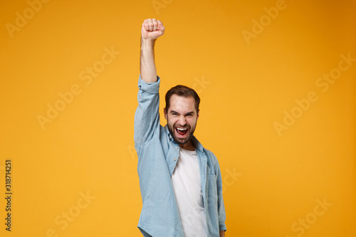 Joyful young bearded man in casual blue shirt posing isolated on yellow orange wall background, studio portrait Obraz na płótnie