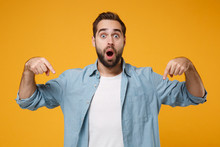 Shocked Young Bearded Man In Casual Blue Shirt Posing Isolated On Yellow Orange Wall Background In Studio. People Lifestyle Concept. Mock Up Copy Space. Pointing Index Fingers Down Keeping Mouth Open.