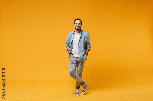 Tela Smiling young bearded man in casual blue shirt posing isolated on yellow orange background, studio portrait