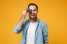 Cheerful Young Man In Casual Blue Shirt Posing Isolated On Yellow Orange Background, Studio Portrait. People Sincere Emotions Lifestyle Concept. Mock Up Copy Space. Covering Eye With Credit Bank Card.
